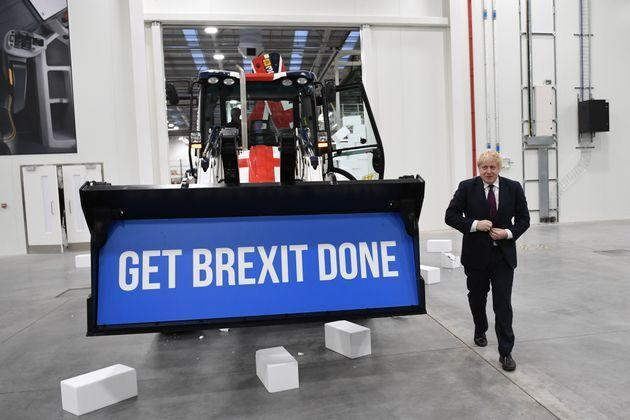 Prime Minister Boris Johnson walks away after driving a Union flag-themed JCB, with the words