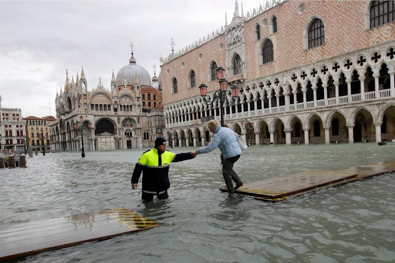 A city worker helps a woman who decided to cross St. Mark's Square on a gangway, in spite of it being closed, in Venice, Italy, on Nov. 17, 2019.  (Photo: ASSOCIATED PRESS)