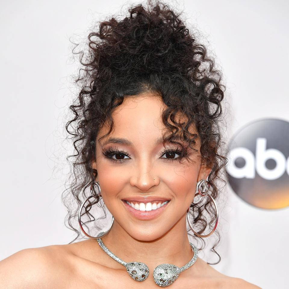 <p>The singer's combination of long lashes, glossy nude lips, and peach blush was the perfect paired-down complement for her curly bun and polka dotted Michael Costello dress.</p>