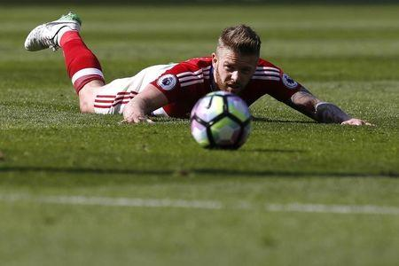 Middlesbrough's Adam Clayton looks at the ball while laying on the pitch