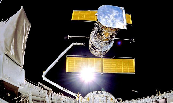 hubble space telesope implements from space shuttle arm in Earth's orbit