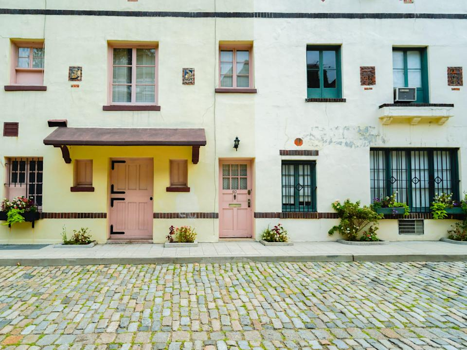 A cobblestone street in front of white residential mews with pink and teal accents.
