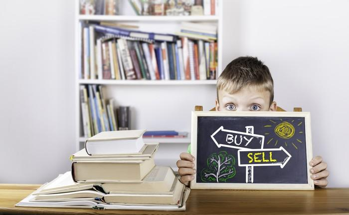 """A child holds a blackboard with """"buy"""" and """"sell"""" signs drawn on it."""