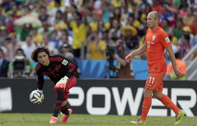 Mexico's goalkeeper Guillermo Ochoa, left, passes the ball to a teammate while Netherlands' Arjen Robben looks on during the World Cup round of 16 soccer match between the Netherlands and Mexico at the Arena Castelao in Fortaleza, Brazil, Sunday, June 29, 2014. At right Netherlands' Arjen Robben.(AP Photo/Marcio Jose Sanchez)