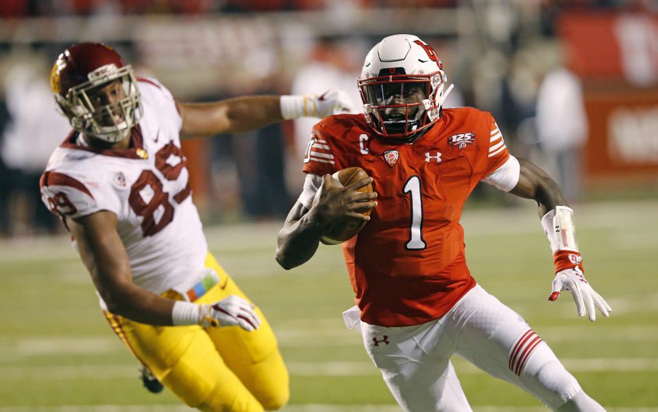 Utah quarterback Tyler Huntley (R) carries the ball in for a touchdown against USC on Saturday. (AP)