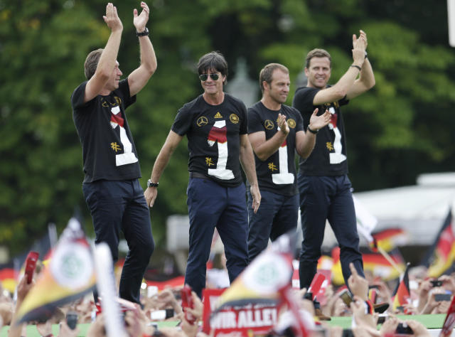 The German coaching team, from left, goalkeeper coach Andreas Koepke, head coach Joachim Loew, assistant coach Hansi Flick and team manager Oliver Bierhoff wave from the stage after the arrival of the German national soccer team in Berlin Tuesday, July 15, 2014. Germany beat Argentina 1-0 on Sunday to win its fourth World Cup title. (AP Photo/Petr David Josek)