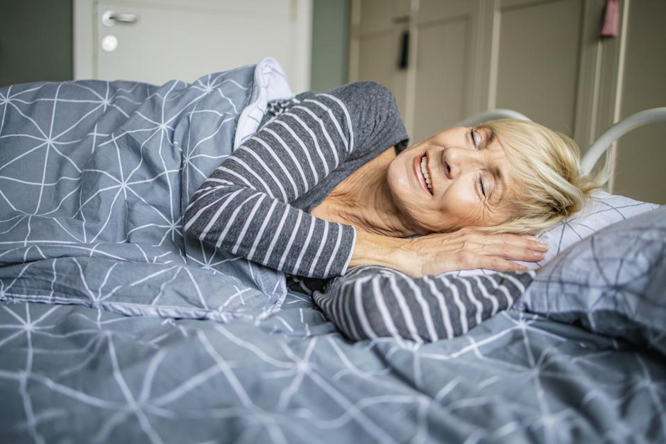 Senior woman is sleeping with smile in bed