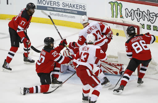 Detroit Red Wings defenseman Patrik Nemeth (22) and left wing Darren Helm (43) watch a shot by New Jersey Devils right wing Wayne Simmonds (17) sail into the net behind Red Wings goaltender Jonathan Bernier as Devils centers Blake Coleman (20) and Jack Hughes (86) look on during the third period of an NHL hockey game, Thursday, Feb. 13, 2020, in Newark, N.J. (AP Photo/Kathy Willens)