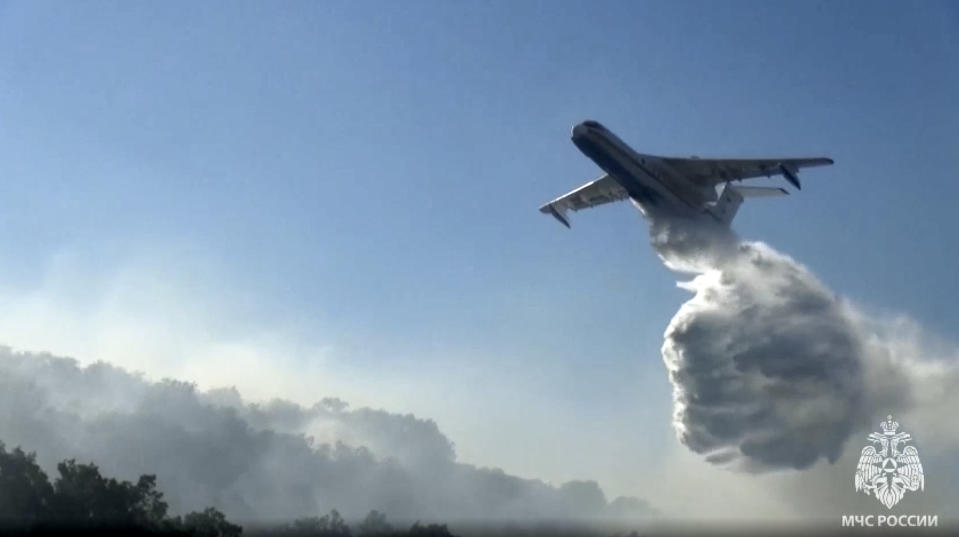 In this photo taken from video released by Russian Emergency Situations Ministry press service, a Russian Emergency Ministry's Beriev multipurpose amphibious aircraft Be-200 drops water during extinguishing a forest fire in the republic of Sakha also knows as Yakutia, Russia Far East, Sunday, July 18, 2021. Russia has been plagued by widespread forest fires, blamed on unusually high temperatures and the neglect of fire safety rules, with Sakha-Yakutia in northeastern Siberia being the worst affected region lately. (Russian Emergency Situations Ministry press service via AP)