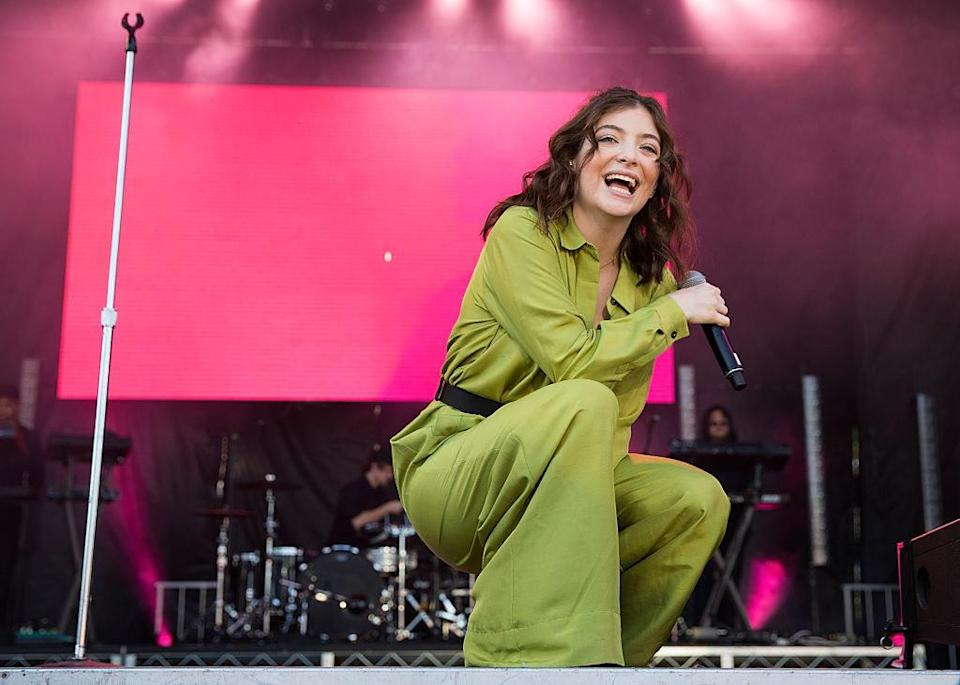 Photo of Lorde performing live in a green jumpsuit