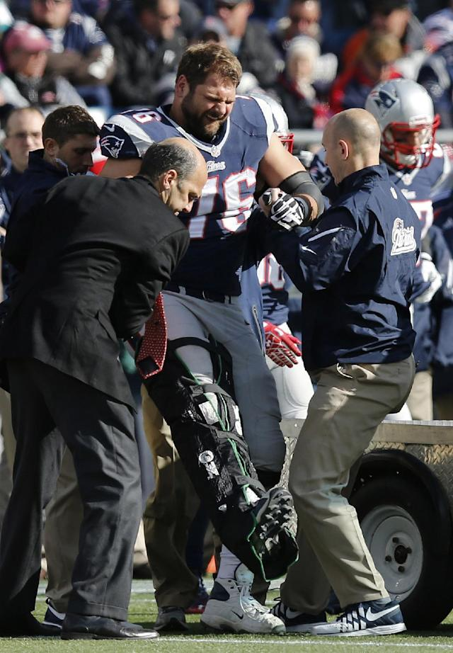 New England Patriots tackle Sebastian Vollmer is tended after an injury in the second quarter of an NFL football game against the Miami Dolphins on Sunday, Oct. 27, 2013, in Foxborough, Mass. (AP Photo/Michael Dwyer)