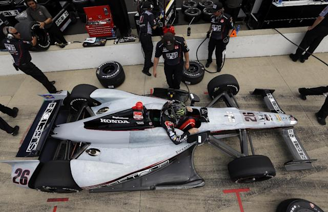In this photo taken on May 11, 2014, Kurt Busch climbs out of his car during practice for Indianapolis 500 IndyCar auto race at the Indianapolis Motor Speedway in Indianapolis. Busch will attempt to drive both the Indianapolis 500 and the NASCAR Coca-Cola 600 in Charlotte on Sunday. (AP Photo/Michael Conroy)