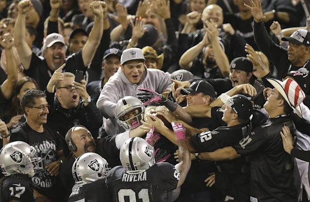 Oakland Raiders wide receiver Rod Streater, bottom center, celebrates with fans and teammates after catching a touchdown pass during the first quarter of an NFL football game against the San Diego Chargers in Oakland, Calif., Sunday, Oct. 6, 2013. (AP Photo/Ben Margot)