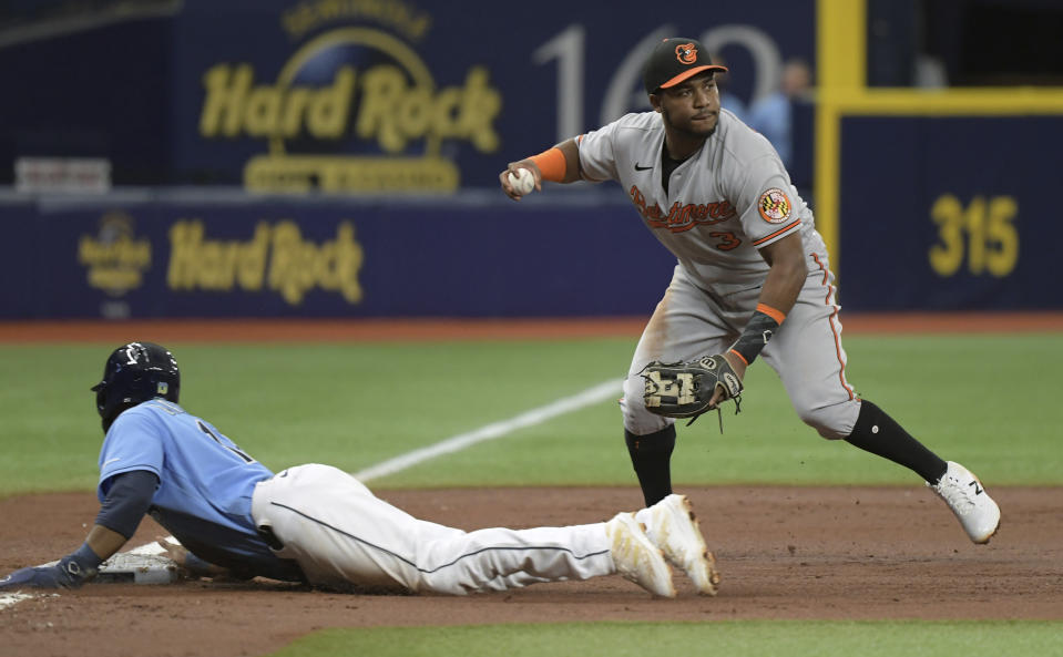 Tampa Bay Rays' Manuel Margot, left, slides into third base on a single hit by Yandy Diaz as Baltimore Orioles' Maikel Franco looks to throw to first base during the third inning of a baseball game Sunday, June 13, 2021, in St. Petersburg, Fla. (AP Photo/Steve Nesius)