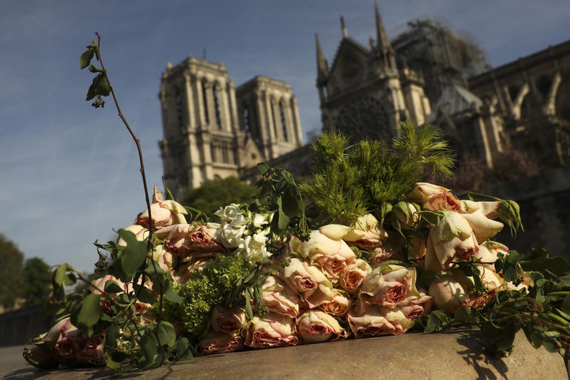 A bunch of flowers lies by the Seine riverside near the Notre Dame cathedral, background, in Paris, Thursday, April 18, 2019. France is paying a daylong tribute Thursday to the Paris firefighters who saved the internationally revered Notre Dame Cathedral from collapse and rescued its treasures from encroaching flames. (AP Photo/Francisco Seco)