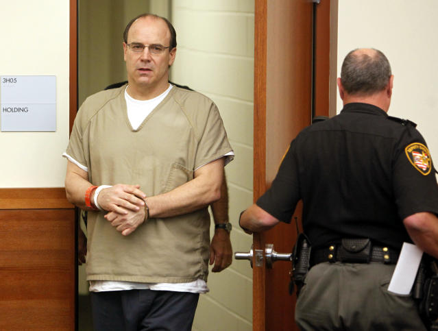 This Thursday, Sept. 15, 2011 file photo shows former Ohio State and NFL quarterback Art Schlichter, left, entering the Franklin County Common Pleas Court in Columbus, Ohio. Multiple individuals defrauded in a scheme perpetrated by an ex-Ohio State and NFL quarterback and his accomplice should receive money from the former player's share of a national concussion settlement, an Ohio prosecutor is arguing. At issue is the case of former star player Schlichter, now serving a nearly 11-year sentence on federal fraud charges. Prosecutors say Schlichter promised college and NFL game tickets, including to the Super Bowl, but never delivered despite receiving thousands of dollars in payments.(AP Photo/Terry Gilliam, File)