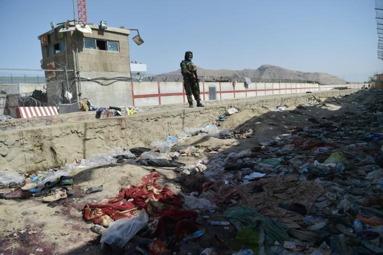 A Taliban fighter stands guard at the site of the suicide bombing outside Kabul airport (AFP/WAKIL KOHSAR)