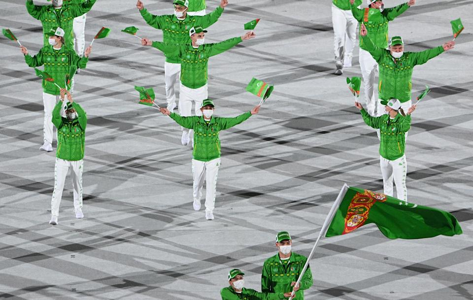 <p>Turkmenistan's flag bearer Gulbadam Babamuratova and Turkmenistan's flag bearer Merdan Atayev lead the delegation during the opening ceremony of the Tokyo 2020 Olympic Games, at the Olympic Stadium, in Tokyo, on July 23, 2021. (Photo by Martin BUREAU / AFP) (Photo by MARTIN BUREAU/AFP via Getty Images)</p>