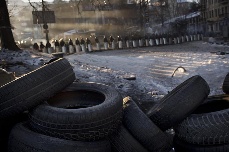 Riot police officers cordon off the area near a barricade heading to Kiev's Independence Square, the epicenter of the country's current unrest, Ukraine, Monday, Feb. 3, 2014. Ukraine's president will return Monday from a short sick leave that had sparked a guessing game he was taking himself out of action in preparation to step down or for a crackdown on widespread anti-government protests. (AP Photo/Emilio Morenatti)