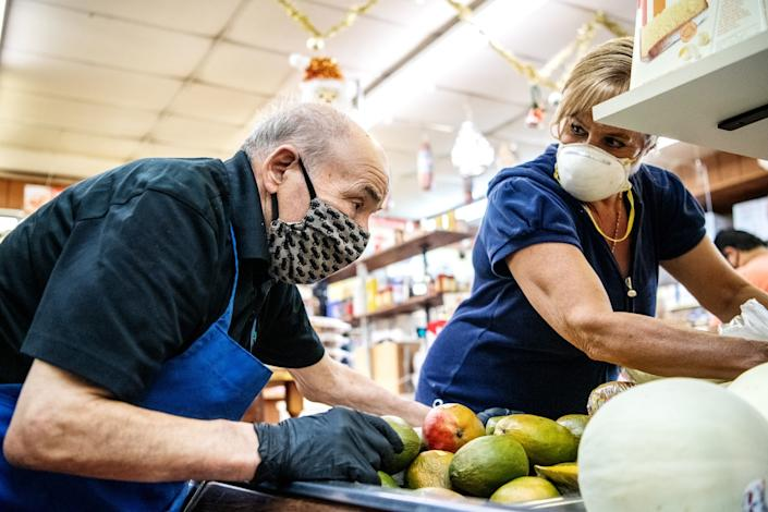 "Roma Market owner Rosario Mazzeo helps a customer select some produce. <span class=""copyright"">(Mariah Tauger / Los Angeles Times)</span>"