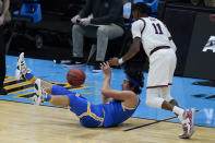 UCLA guard Jaime Jaquez Jr., left, picks up a loose ball ahead of Gonzaga guard Joel Ayayi (11) during the first half of a men's Final Four NCAA college basketball tournament semifinal game, Saturday, April 3, 2021, at Lucas Oil Stadium in Indianapolis. (AP Photo/Darron Cummings)