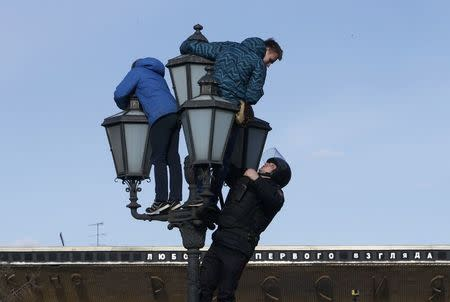 A riot police officer climbs on a lamp pole to detain opposition supporters during a rally in Moscow, Russia March 26, 2017. REUTERS/Sergei Karpukhin