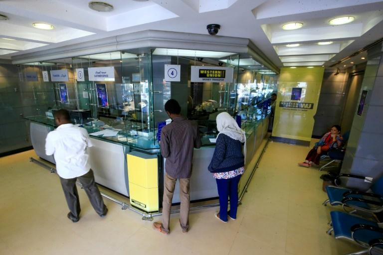 Sudanese wait in January 2020 to exchange money in the capital Khartoum, which has been pushing for a removal from the US list of state sponsors of terrorism