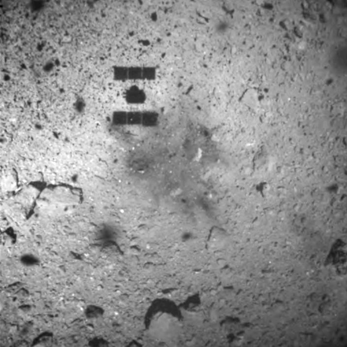FILE - This Feb. 22, 2019, file image released by the Japan Aerospace Exploration Agency (JAXA) shows the shadow, center above, of the Hayabusa2 spacecraft after its successful touchdown on the asteroid Ryugu. The Hayabusa2 spacecraft left the asteroid Ryugu, about 300 million kilometers (180 million miles) from Earth, a year ago and is expected to reach Earth and drop a capsule containing the precious samples in southern Australia on Dec. 6. (JAXA via AP, File)