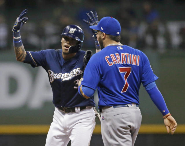 Milwaukee Brewers' Orlando Arcia reacts next to Chicago Cubs' Victor Caratini (7) after hitting a double during the seventh inning of a baseball game Tuesday, Sept. 4, 2018, in Milwaukee. (AP Photo/Aaron Gash)