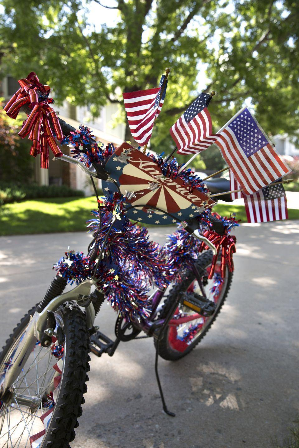 """<p>Your family can have your very own parade by decorating your bikes with flags, streamers, and ribbons, and setting off together for a few casual laps around the block. The ride will help everyone work up an appetite before the celebratory barbecue. </p><p><a class=""""link rapid-noclick-resp"""" href=""""https://www.amazon.com/White-Patriotic-Crepe-Paper-Streamers/dp/B00BFX7AEU/?tag=syn-yahoo-20&ascsubtag=%5Bartid%7C10050.g.4463%5Bsrc%7Cyahoo-us"""" rel=""""nofollow noopener"""" target=""""_blank"""" data-ylk=""""slk:SHOP 4TH OF JULY STREAMERS"""">SHOP 4TH OF JULY STREAMERS</a></p>"""