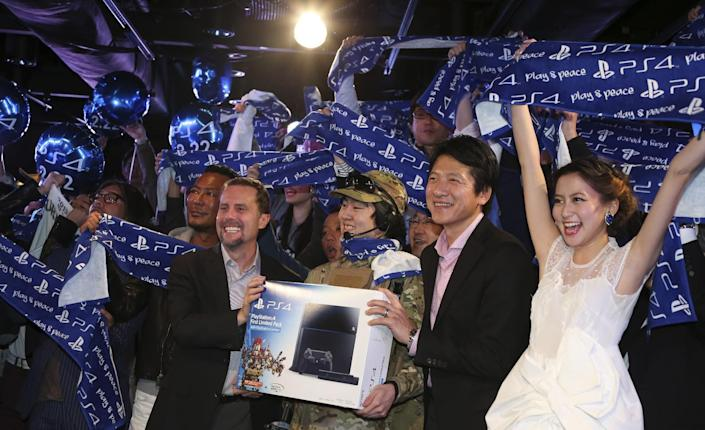 Sony Computer Entertainment Inc. President and CEO Andrew House, second left, Sony Computer Entertainment Japan President Hiroshi Kawano, second from right, fashion model Mayuko Kawakita, right, and first customer of PlayStation 4 , center, pose for photo during launch event in Tokyo, Saturday, Feb. 22, 2014. (AP Photo/Koji Sasahara)