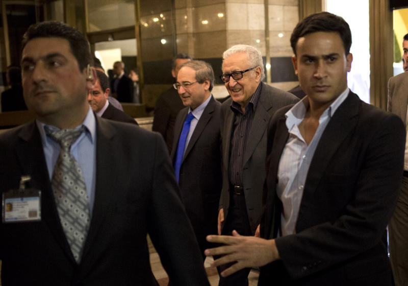 U.N.-Arab League envoy Lakhdar Brahimi, center right, and Deputy Syrian Foreign Minister Faisal Mekdad arrive to a hotel surrounded by security Monday, Oct. 28, 2013 in Damascus, Syria. Brahimi is on his first trip to the country in almost a year. (AP Photo/Dusan Vranic)