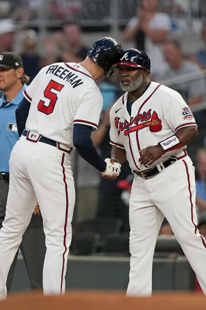 Atlanta Braves first baseman Freddie Freeman (5) touches helmets with first base coach Eric Young Sr. (2) after an RBI single in the first inning of a baseball game against the Colorado Rockies Tuesday, Sept. 14, 2021, in Atlanta. (AP Photo/John Bazemore)
