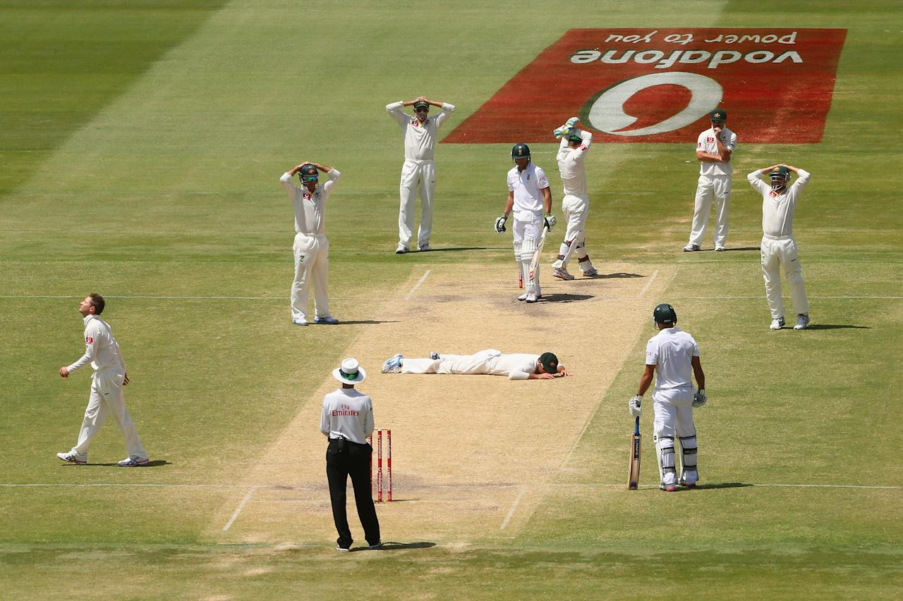Australia fielder Rob Quiney lies on the pitch after missing a catch off South Africa's Faf du Plessis during day five of the Second Test Match between Australia and South Africa at Adelaide Oval on November 26, 2012 in Adelaide, Australia.