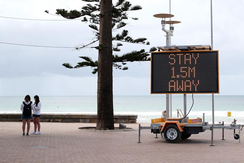 A sign reminding residents and tourists of new social distancing rules is displayed at Manly Beach.