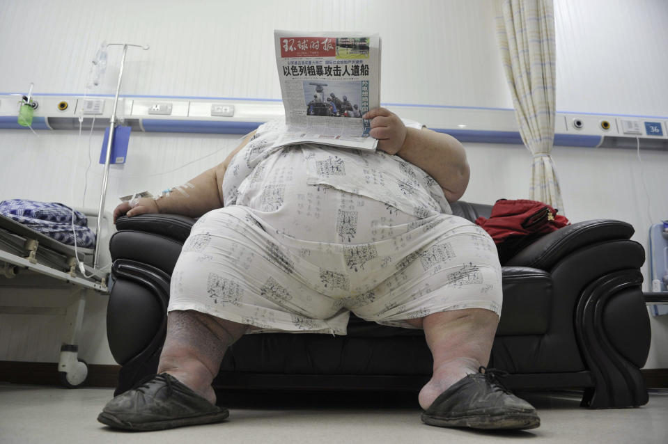 Liang Yong, 30, who weighs about 230 kg (507 lbs) and is 1.58 m (5.18 ft) tall, reads newspaper in a ward at a hospital in Chongqing municipality June 1, 2010. Liang, who has suffered from obesity since 1998 and has unsuccessfully tried different methods of losing weight, is in a critical health condition due to his weight, and has been warded in the intensive care unit since last week, local media reported. REUTERS/Stringer (CHINA - Tags: HEALTH SOCIETY) CHINA OUT. NO COMMERCIAL OR EDITORIAL SALES IN CHINA