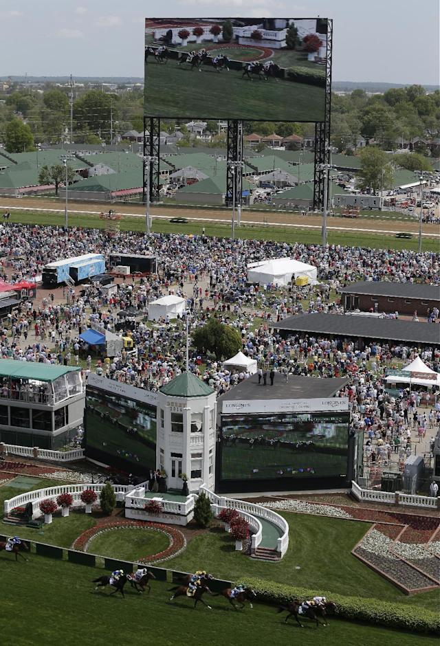 Fans watch a race on a large video screen before the 140th running of the Kentucky Derby horse race at Churchill Downs Saturday, May 3, 2014, in Louisville, Ky. (AP Photo/Charlie Riedel)