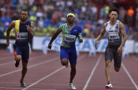Michael Rodgers from USA, center, goes to win the men's 100 meters event, as Andre De Grasse from Canada, left, finnishes second and Xie Zhen Ye finnishes third at the Golden Spike athletics IAAF World Challenge in Ostrava, Czech Republic, Thursday, June 20, 2019 (Jaroslav Ozana/CTK via AP)
