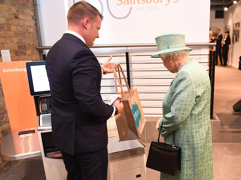 Queen Elizabeth II is shown a modern self service till as she views a replica of one of the original Sainsbury's stores during a visit to Covent Garden, London. The event marked the 150th anniversary of the supermarket chain first opening.