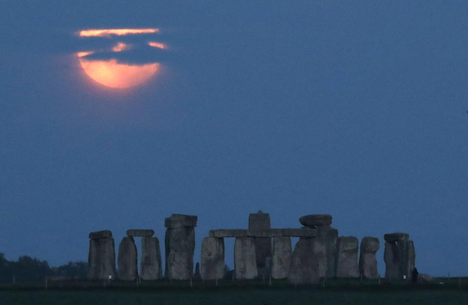 """<p>The full moon, known as the """"Super Flower Moon"""", is seen behind Stonehenge stone circle near Amesbury, Britain, May 26, 2021. REUTERS/Peter Cziborra</p>"""
