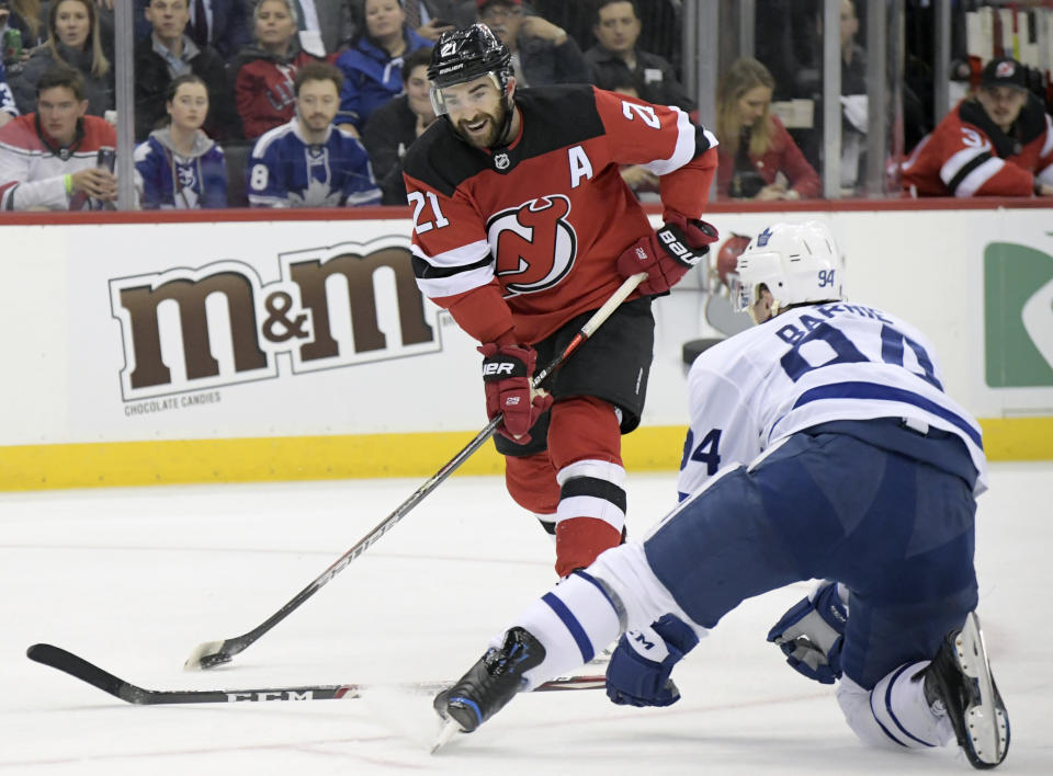 New Jersey Devils right wing Kyle Palmieri (21) shoots as Toronto Maple Leafs defenseman Tyson Barrie (94) defends during the second period of an NHL hockey game Friday, Dec. 27, 2019, in Newark, N.J. (AP Photo/Bill Kostroun)