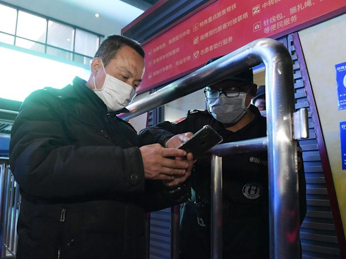 A staff member helps a passenger scan health codes at Wuchang Railway Station in Wuhan on April 8, 2020.