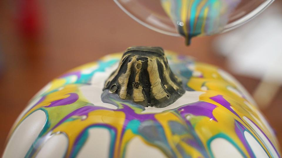 <p>Place your pumpkin on a paper plate or newspaper to protect your tabletop from spillage, then slowly pour the cup of paints over the pumpkin, carefully drizzling around the stem until you achieve your desired look. You can have as much or as little coverage as you want, so go with your gut and pour as much paint as you think looks nice. </p>