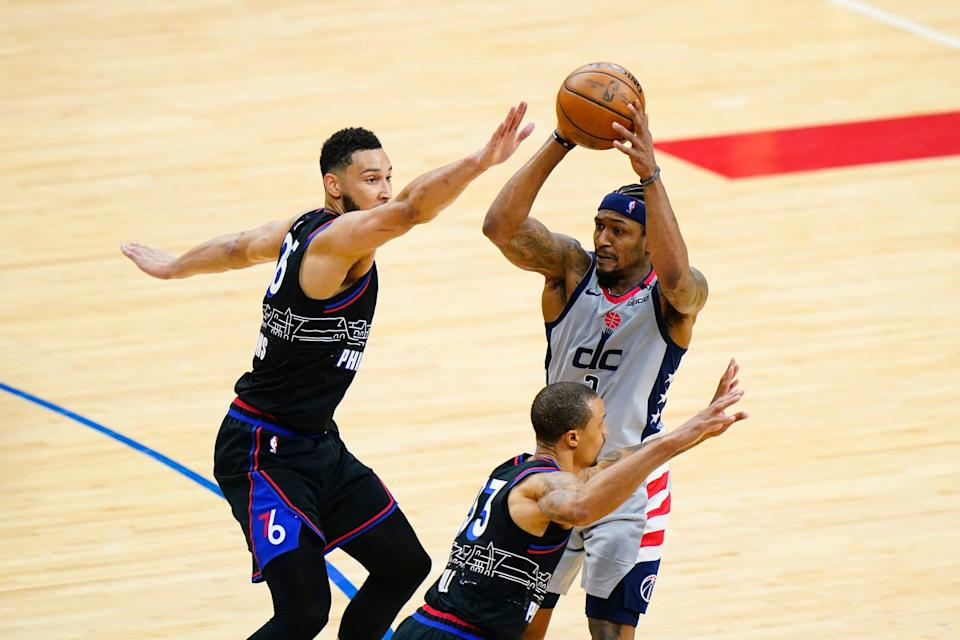 The Wizards' Bradley Beal, right, tries to pass against the 76ers' Ben Simmons, left, and George Hill during Game 1.