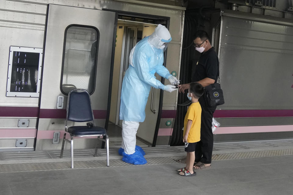 A health worker checks oxygen level for a COVID-19 patient upon his arrival at Rangsit train station in Pathum Thani province, Thailand, Tuesday, July 27, 2021. Thai authorities began transporting some people who have tested positive with the coronavirus from Bangkok to their hometowns on Tuesday for isolation and treatment, to alleviate the burden on the capital's overwhelmed medical system. (AP Photo/Sakchai Lalit)