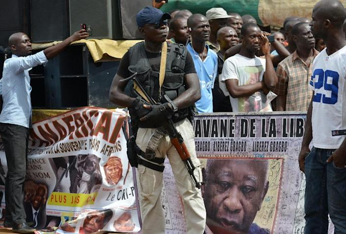 An armed man stands next to a banner featuring former Ivory Coast President Laurent Gbagbo during a meeting of the National Coalition for Change (CNC) party, on October 7, 2015 in Yopougon (AFP Photo/Issouf Sanogo)