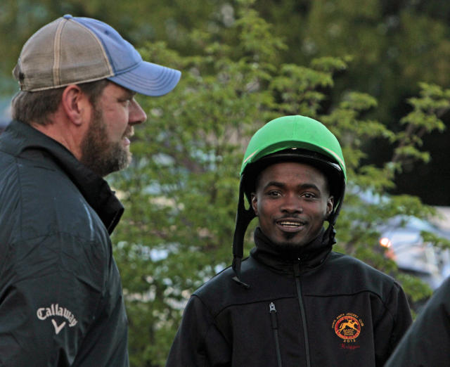 Jockey Kevin Krigger, right, talks with trainer Doug O'Neill, left, as they watch horses work out at Churchill Downs, Sunday, April 28, 2013, in Louisville, Ky. Krigger is to ride Kentucky Derby hopeful Goldencents for O'Neill in the race. (AP Photo/Garry Jones)