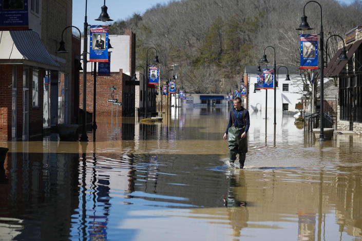 Brad Newnam, of Beattyville, Ky., crosses a flooded East Main Street while checking on businesses in the area in downtown Beattyville, Ky., Tuesday, March 2, 2021. Heavy rains caused the Kentucky River to flood most of downtown Beattyville. (Alex Slitz/Lexington Herald-Leader via AP)
