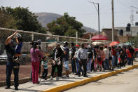 Residents wait in line for a chance to try out a new public transit system dubbed the Cablebus, outside the Campos Revolucion station in the Cuautepec neighborhood of northern Mexico City, Thursday, March 4, 2021. For the residents of Cuautepec, this new system, the first of four planned lines, will turn a commute to the nearest subway station, that can last up to two hours, into a 30-minute ride. (AP Photo/Rebecca Blackwell) northern Mexico City, Thursday, March 4, 2021. (AP Photo/Rebecca Blackwell)