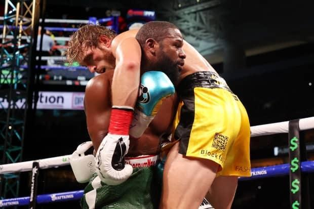 Logan Paul is draped over Floyd Mayweather during their exhibition fight in Miami on Sunday. (Getty Images - image credit)